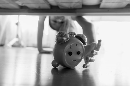 Black and white image of beautiful girl reaching for alarm clock under the bed