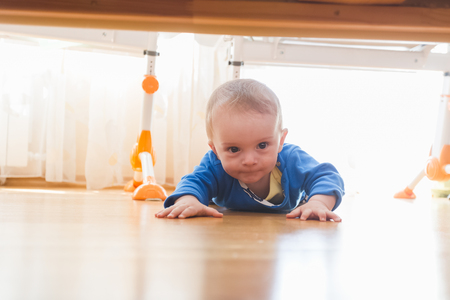 nappy new year: Cute baby boy crawling and looking under the bed Stock Photo