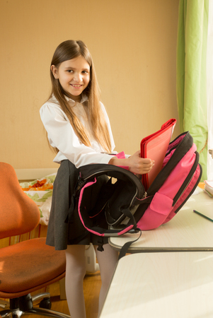 Mooi meisje in school uniform poseren met zak