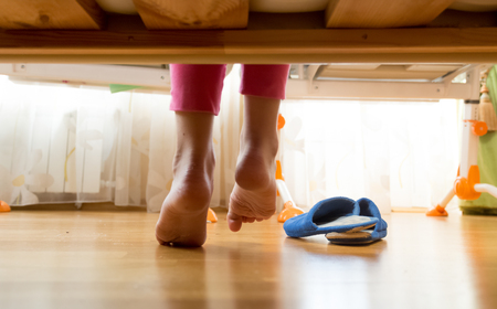 Closeup photo of female feet under the bed