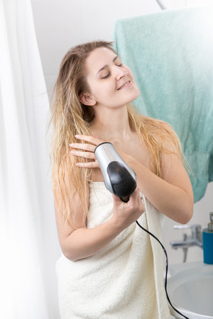 Beautiful woman covered in bath towel with hairdryer at bathroom Stock Photo