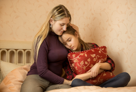 Young mother embracing and solacing teenage daughter 스톡 콘텐츠