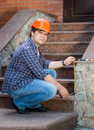 sealant: Smiling male worker measuring stone staircase with measuring tape