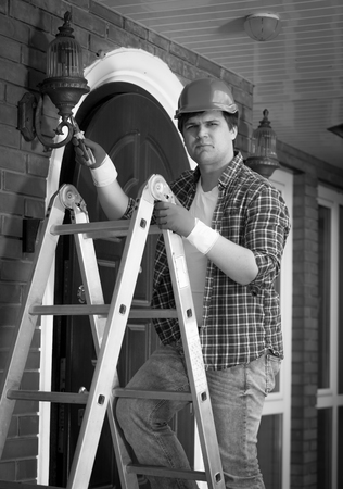 Black and white portrait of electrician posing on stepladder
