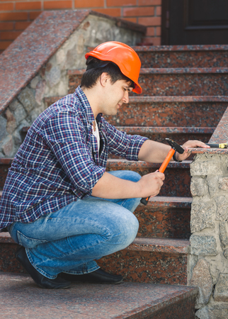 sealant: Smiling construction worker repairing stone staircase