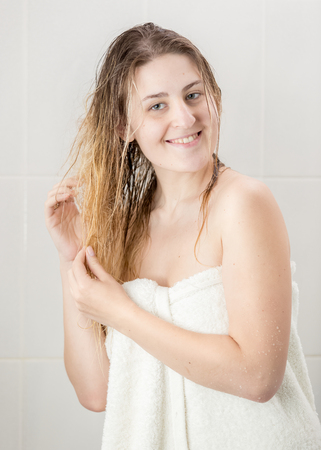 Portrait of smiling woman with long hair covered in towel