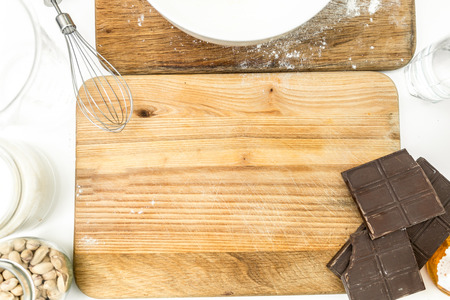 pin board: Closeup photo of rolling pin, chocolate, flour and dough lying on wooden board at kitchen Stock Photo
