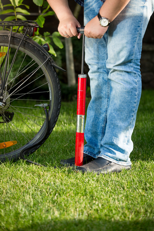 Young man pumping bicycle wheel on grass