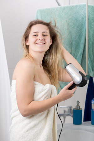 Portrait of smiling young woman drying long hair at bathroom Stock Photo