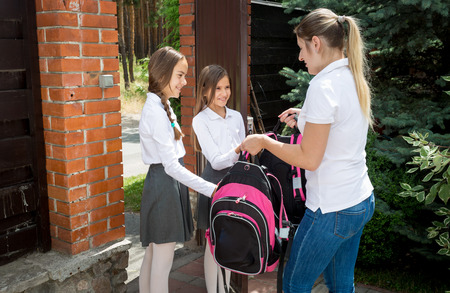 Beautiful young woman seeing off her daughters to school at morning Standard-Bild