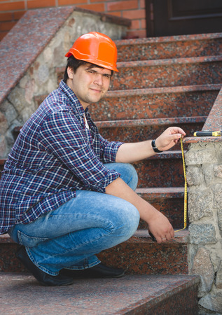 sealant: Worker in red helmet repairing old stone staircase Stock Photo