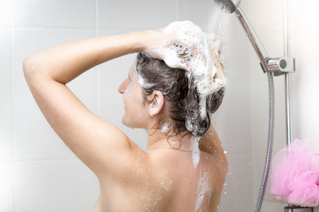 female in douche: Woman washing head with shampoo in shower