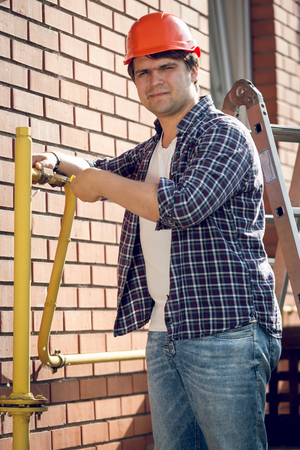 Portrait of smiling plumber repairing pipes