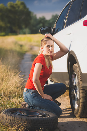 Sad woman got confused about changing flat tire in the field Stock Photo
