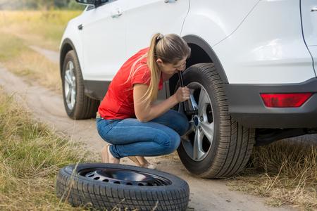 フィールドにタイヤがパンクを変更する若い女性