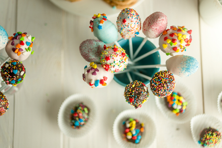 Decorated candies and cake pops on wooden boards Stock Photo