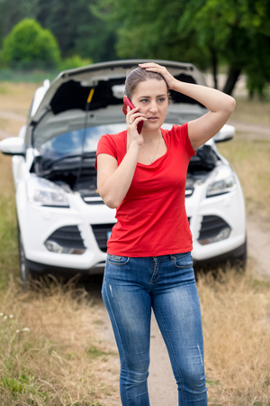 waiting phone call: Frustrated young woman calling for help with her broken car
