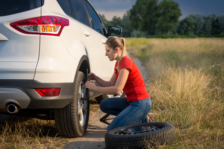 Young woman changing car wheel on the rural road going through field