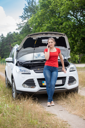 Beautiful woman leaning on broken car and talking by phone