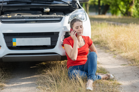 Young female driver sitting on ground next to broken car and calling for help