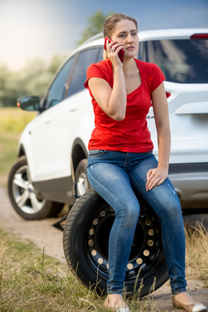 jack tar: Woman sitting on the spare tire at roadside and calling for help