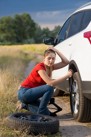 Woman unscrewing nuts on car flat wheel at field Stock Photo