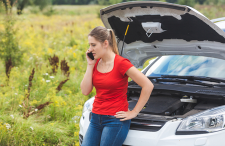 Woman leaning on broken car and calling for help by mobile phone Stock Photo