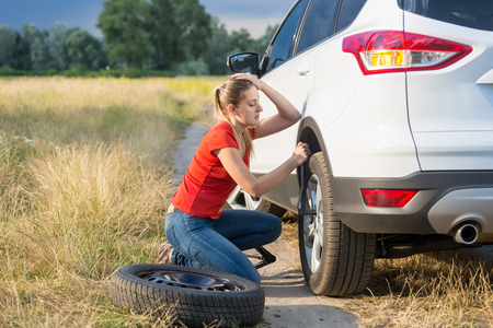 Sad woman replacing car flat tire at field