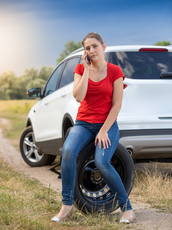 Young female driver sitting next broken car at field and talking by phone Stock Photo