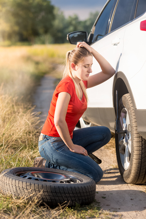 Woman sitting at broken car and trying to change flat tire Stock Photo
