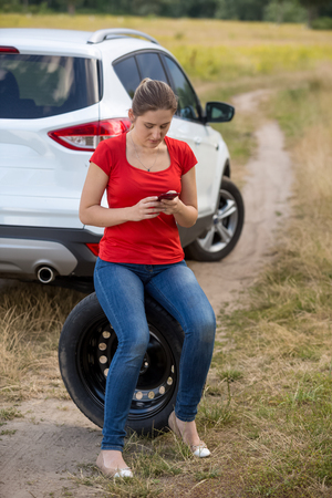 jack tar: Young upset woman siting on spare tire next to broken car at field and searching for service phone number