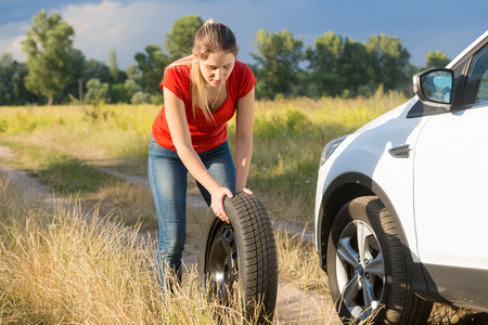 Beautiful woman rolling spare tire to change the flat one