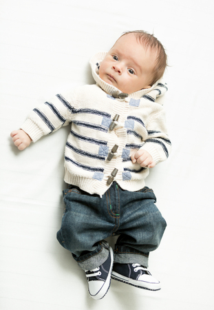 nappy new year: Cute baby boy in jeans and sweater lying on bed Stock Photo