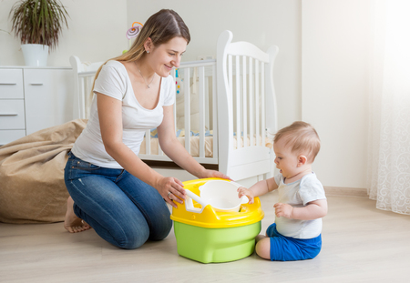 Young smiling mother sitting on floor at living room and teaching her baby boy how to use chamber pot