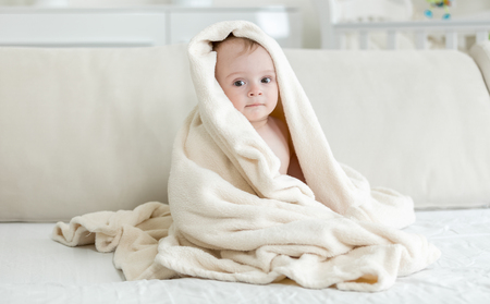 one sheet: Baby boy covered in big towel after bathing Stock Photo