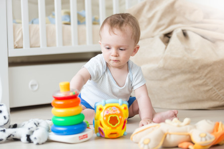 Cute baby boy assembling colorful toy tower on floor