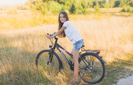 Beautiful teenage girl sitting on bicycle at meadow