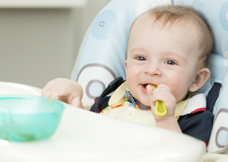 Adorable 9 months old boy eating in highchair at kitchen