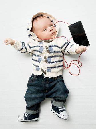 Cute baby boy listening music with earphones