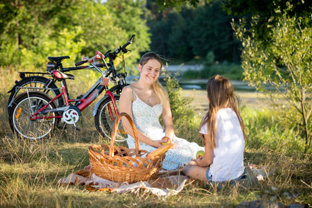 niños platicando: 10 year old girl having picnic by the river with young mother Foto de archivo