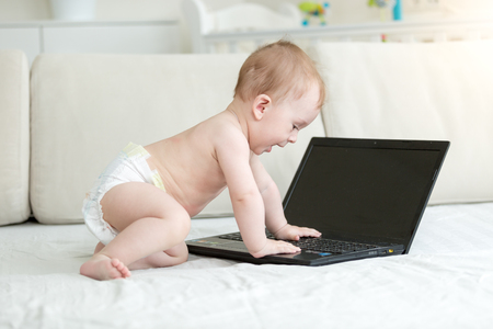 nude little girls: Smart baby in diapers sitting on bed and using laptop Stock Photo