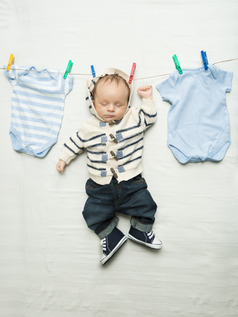Funny photo of cute baby boy hanging on clothesline