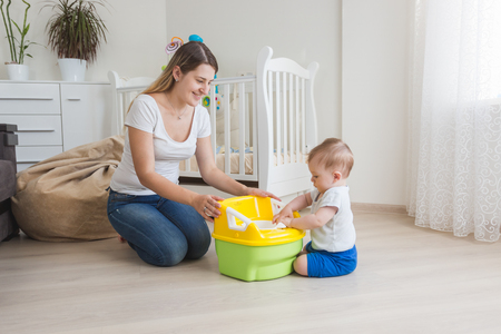 Loving mother teaching her baby boy how to use chamber pot