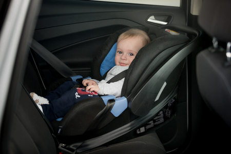 fasten: Little smiling baby on back seat Stock Photo