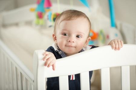 teething: Portrait of 9 month old boy standing in white cradle