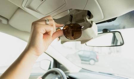 Vrouw die zonnebril uit een speciale auto compartiment brengt Stockfoto
