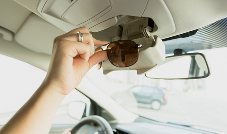 Woman taking sunglasses out of special car compartment