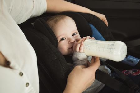 車の後部座席の上にボトルからミルクを飲む男の子の赤ちゃんの肖像画
