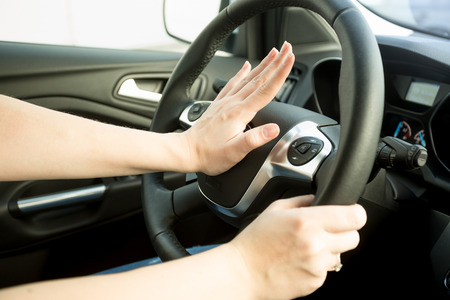 Closeup image of annoyed woman driving car and honking Stock Photo