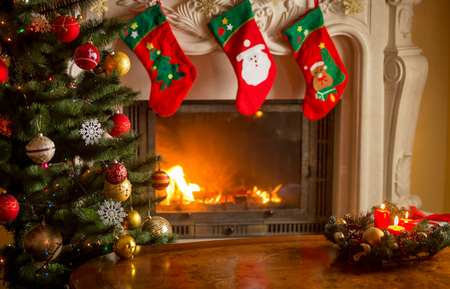 Empty wooden table in front of decorated fireplace and Christmas tree. Place for text. Stock Photo